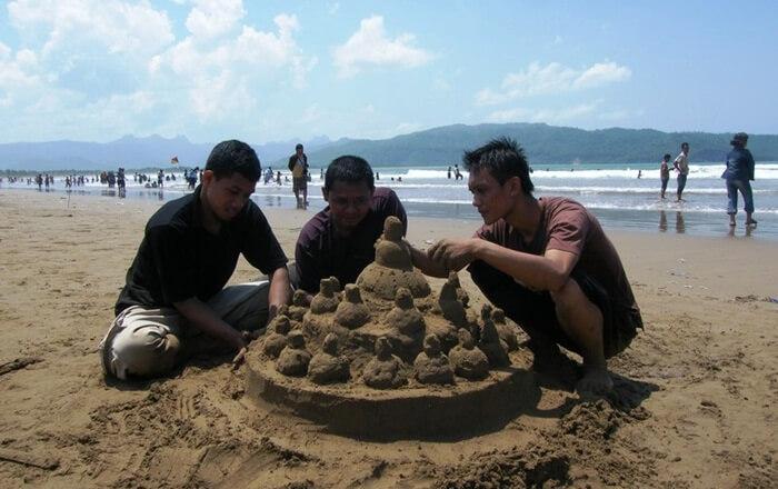 Main pasir di pantai teleng ria bukan hanya monopoli anak anak. dewasa pun bsia menikmati permainan ini