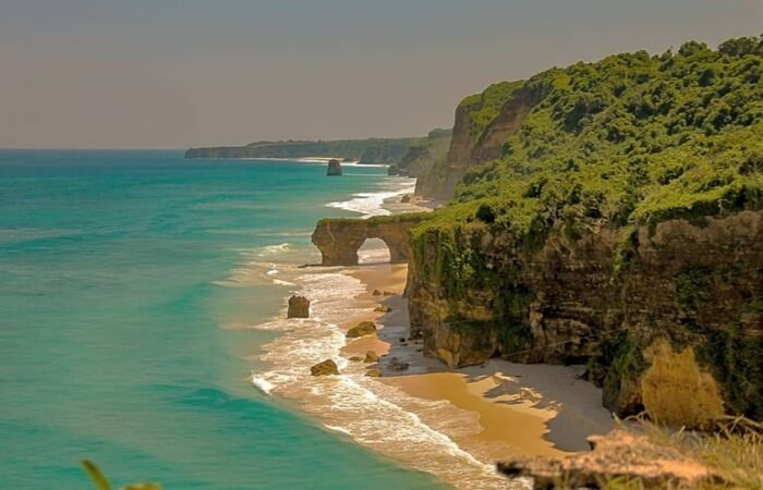"Pantai Mbawana yang berada di Kecamatan Kodi Balagahar, menyuguhkan keindahan alam yang sangat mempesona. Pantai ini berupa hamparan pasir putih yang lembut dengan deretan tebing tinggi yang indah dengan ""gapura"" laut nya."